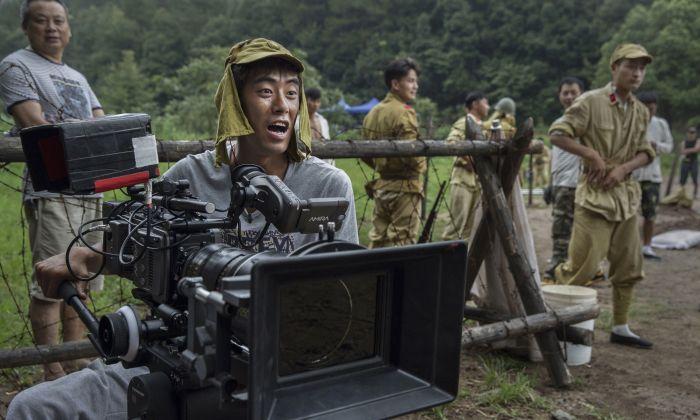 """Un director de fotografía chino lleva un sombrero del ejército japonés durante el rodaje de la serie """"El Último Noble"""", ambientada durante la segunda guerra sino-japonesa en Fangyan, China, el 13 de agosto de 2015. (Kevin Frayer/Getty Images)"""