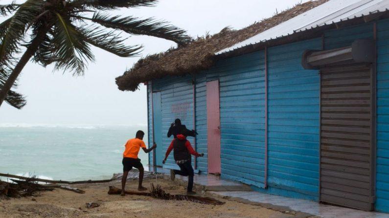 Jóvenes se cubren de los fuertes vientos que azotan la ciudad costera de Punta Cana, en la República Dominicana, cuando se acercaba el huracán María el 20 de septiembre de 2017. (ERIKA SANTELICES/AFP/Getty Images)