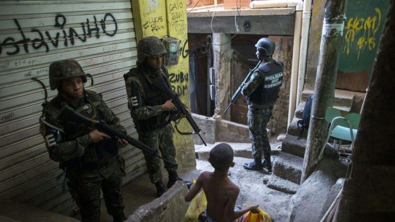 TOPSHOT - Employing urban combat tactics, Brazilian army military police personnel patrol along an alley in the Rocinha favela in Rio de Janeiro, Brazil on September 25, 2017.  Policía militar del ejército brasileño patrulla a lo largo de un callejón en la favela de Rocinha en Río de Janeiro, Brasil, el 25 de septiembre de 2017. (MAURO PIMENTEL/AFP/Getty Images)