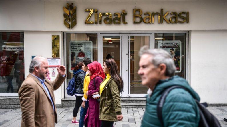 La gente camina por una sucursal del banco turco Ziraat en la avenida Istiklal en Estambul en una imagen de archivo del 1 de diciembre de 2017. (OZAN KOSE / AFP / Getty Images)