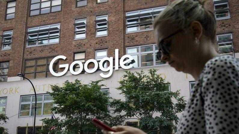 Una mujer mira su teléfono inteligente mientras pasa junto al Edificio 8510 de Google en 85 10th Ave. en la ciudad de Nueva York el 3 de junio de 2019. (Drew Angerer/Getty Images)