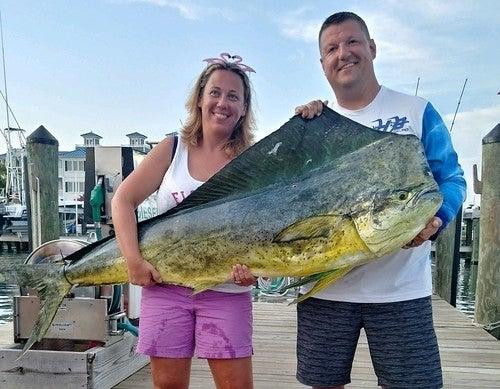 Kristy Frashure posa con su esposo, Ryan, y el Dorado que batió el récord en Ocean City el 16 de agosto de 2019. (Departamento de Recursos Naturales de Maryland)