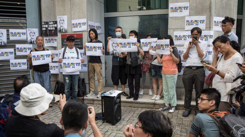 Personas sostienen un retrato del trabajador del consulado británico Simon Cheng, durante una reunión para solicitar al gobierno británico que ayude en su liberación, fuera del Consulado Británico en Hong Kong el 21 de agosto de 2019. (Chris McGrath/Getty Images)