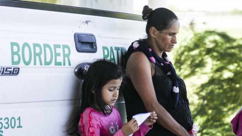 Una mujer embarazada y una niña se apoyan contra un camión de la Patrulla Fronteriza luego de ser detenidas por cruzar ilegalmente la frontera de los Estados Unidos sobre el Río Grande desde México cerca de McAllen, Texas, el 18 de abril de 2019. (Charlotte Cuthbertson/La Gran Época)