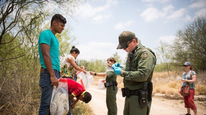 Los agentes de la Patrulla Fronteriza hacen que los extranjeros se quiten los cordones de sus zapatos y sus pertenencias antes de subirlos en una camioneta en el condado de Hidalgo, Texas, el 26 de mayo de 2017. (Benjamin Chasteen/La Gran Época)