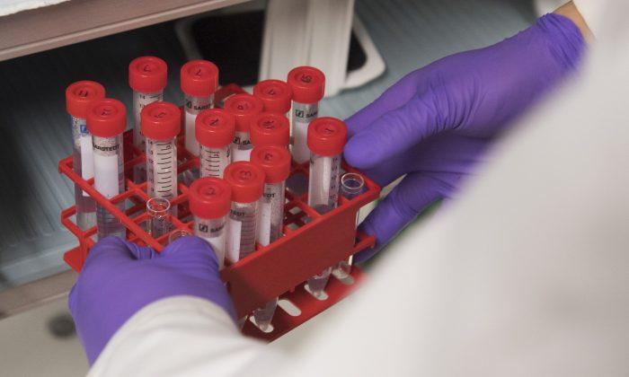 Um biólogo segura tubos de ensaio enquanto trabalha em um laboratório no Instituto Nacional do Câncer nos Institutos Nacionais de Saúde em Bethesda, Maryland, em 7 de fevereiro de 2018 (Saul Loeb / AFP / Getty Images)