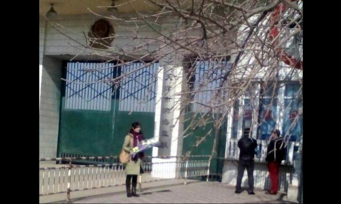 Ge Xiulan parada afuera de la prisión de Binhai con unas flores para su esposo encarcelado el día de su cumpleaños en 2018. Las autoridades de la prisión no le permitieron visitarlo ese día. (Minghui.org)