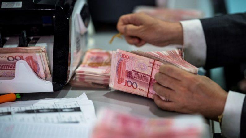 Un empleado del banco cuenta billetes de 100 yuanes (USD 14.3) en un banco en Shanghai el 8 de agosto de 2018. (JOHANNES EISELE/AFP/Getty Images)