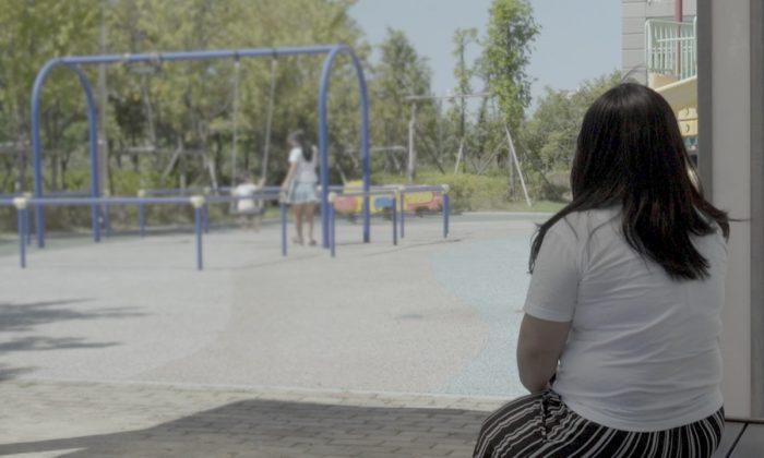 """""""Yoon Su Ryun"""" foi sexualmente agredida enquanto esteve detida na Coreia do Norte, antes de sua fuga. Ela foi fotografada observando a filha e a sobrinha em um parque infantil na Coreia do Sul, em 28 de agosto de 2018 (© Human Rights Watch )"""