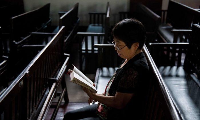 Una mujer lee la Biblia en la iglesia de la Gloria Cristiana en Wuhan, una ciudad de la provincia china de Hebei, el 23 de septiembre de 2018. (Nicolas Asfouri/AFP/Getty Images)