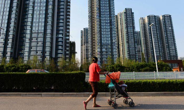 Imagen de archivo de una mujer cruzando una calle con un cochecito en China. (STR/AFP/Getty Images)