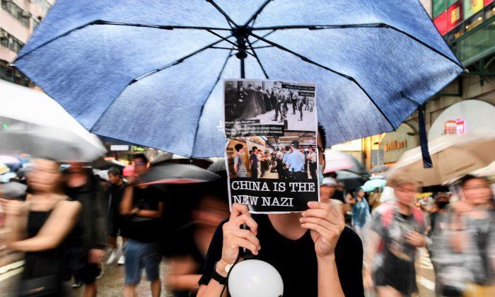 HONG KONG, CHINA : Manifestantes caminan delante de un graffiti durante un mitin en Chartered Garden en Hong Kong, China, el 16 de agosto de 2019. Desde el 9 de junio, los manifestantes a favor de la democracia han seguido manifestándose en las calles de Hong Kong contra un controvertido proyecto de ley de extradición mientras la ciudad se sumergía en una crisis tras oleadas de manifestaciones y varios enfrentamientos violentos. . (Foto de Anthony Kwan/Getty Images)