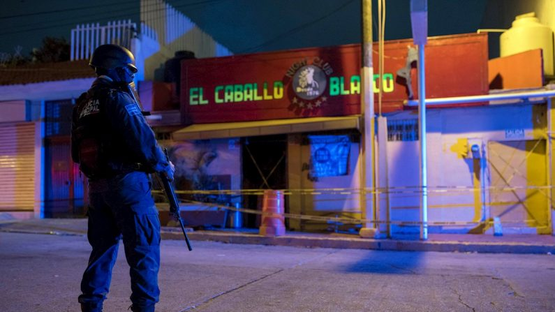 Un agente de la policía custodia en las primeras horas frente del bar El Caballo Blanco, atacado por un grupo armado, en Coatzacoalcos, en el estado de Veracruz (México) el 28 de agosto de 2019. EFE/ Ángel Hernández