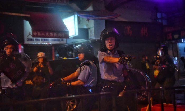Agentes de policía apuntan con sus armas a los manifestantes en Tseun Wan, Hong Kong, el 25 de agosto de 2019. (Lillian Suwanrumpha/AFP/Getty Images)