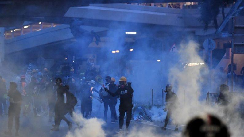 Manifestantes devuelven latas de gas lacrimógeno disparadas por la policía en Tai Wai, en los Nuevos Territorios de Hong Kong, el 10 de agosto de 2019. (Manan Vatsyayana/AFP/Getty Images)