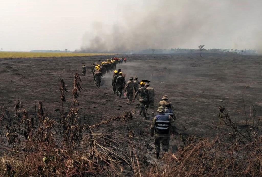 Bombeiros caminham por um campo queimado enquanto combatem um incêndio em Robore, no leste da Bolívia, em 23 de agosto de 2019 (STR / AFP / Getty Images)