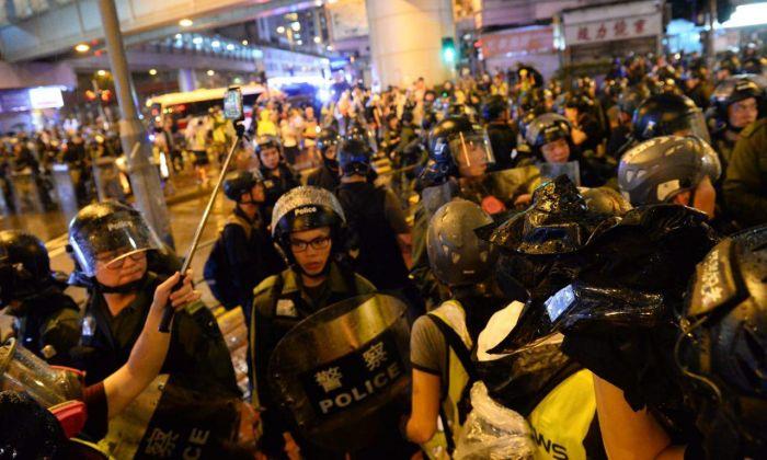 La policía de Hong Kong se enfrenta a los manifestantes en Sha Tsui Road la noche del 25 de agosto de 2019. (Song Bilong/The Epoch Times)