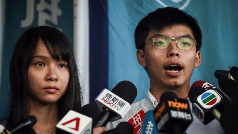 Los activistas prodemocráticos Agnes Chow (izq.) y Joshua Wong (der.) hablan con la prensa luego de ser liberados bajo fianza en los tribunales de magistrados del este en Hong Kong el 30 de agosto de 2019. (Lillian Suwanrumpha/AFP/Getty Images)