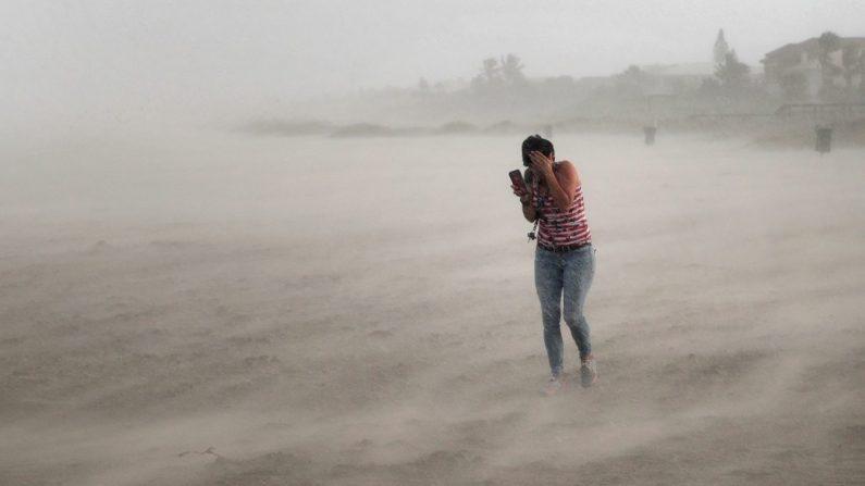 Una mujer busca protegerse del viento, la arena que sopla y la lluvia azotada por el huracán Dorian mientras camina por la playa en Cocoa Beach, Florida, el 2 de septiembre de 2019. (Scott Olson/Getty Images)