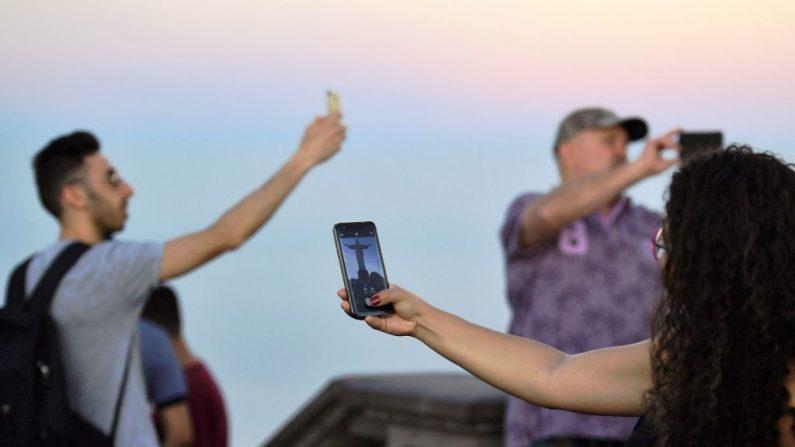 Turistas sacan fotos en la estatua del Cristo Redentor, el 13 de junio de 2019. (CARL DE SOUZA/AFP/Getty Images)