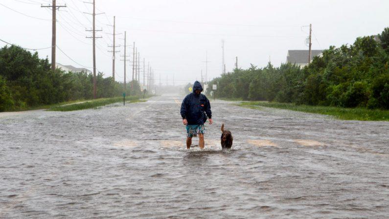 Una persona camina con su perro por un camino inundado en Salvo, Carolina del Norte, mientras el huracán Dorian golpea el 6 de septiembre de 2019. (JOSE LUIS MAGANA/AFP/Getty Images)
