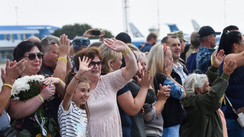 Amigos y familiares saludan mientras un avión que transporta a exprisioneros aterriza el 7 de septiembre de 2019 en el aeropuerto internacional de Boryspil en Kiev. (SERGEI SUPINSKY/AFP/Getty Images)