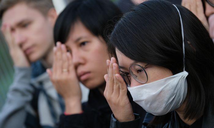 Manifestantes frente a la Cancillería en Berlín, Alemania, se tapan un ojo en alusión a una manifestante herida en Hong Kong mientras instan a la Canciller alemana Angela Merkel a mostrar solidaridad con las manifestaciones en Hong Kong a favor de la democracia, el 5 de septiembre de 2019. (Sean Gallup/Getty Images)