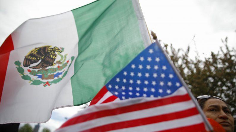 Un manifestante sostiene las banderas de los Estados Unidos y México durante las manifestaciones del 1 de mayo en Chicago, 1 de mayo de 2017. (Jim Young/AFP/Getty Images)