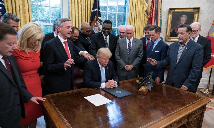 El presidente Donald Trump y líderes religiosos oran en el Despacho Oval el 1 de septiembre en la Casa Blanca después de que Trump firmara una proclamación declarando al día nacional de oración, el 3 de septiembre (NICHOLAS KAMM/AFP/Getty Images)