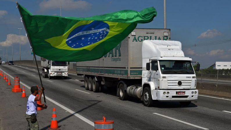 Hombre ondea la bandera nacional brasileña frente a la refinería Duque de Caxias en el área metropolitana de Río de Janeiro, Brasil, el 28 de mayo de 2018. (CARL DE SOUZA/AFP/Getty Images)