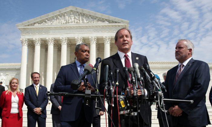 El Fiscal General de Texas, Ken Paxton, habla mientras el Fiscal General de Washington, Karl Racine (izq.), escucha durante una conferencia de prensa frente a la Corte Suprema de Estados Unidos en Washington el 9 de septiembre de 2019. (Alex Wong/Getty Images)