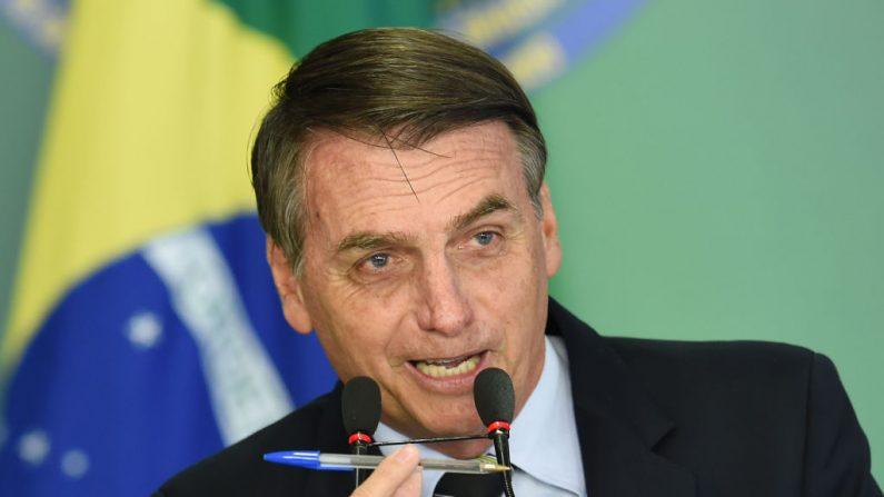 Presidente brasileiro Jair Bolsonaro discursa e mostra a caneta que usou para assinar o decreto presidencial que flexibiliza a posse de armas de fogo, no Palácio do Planalto, em Brasília, em 15 de janeiro de 2019 (EVARISTO SA / AFP / Getty Imagens)