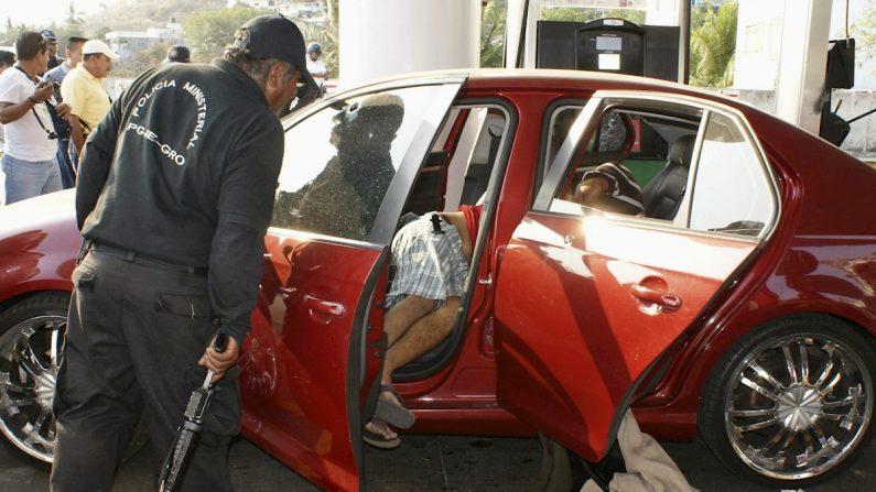 Un agente ministerial observa un cadaver el miércoles 5 de mayo de 2010, en el interior de un vehículo en donde cuatro personas, entre ellas un niño, fueron asesinadas por un grupo de hombres armados en una estación de gasolina en el puerto de Acapulco, en el Pacífico mexicano. EFE/Jesús Espinosa/Archivo