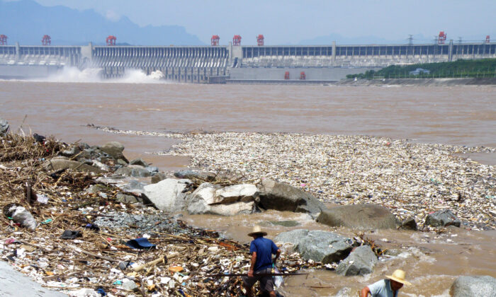 Dos trabajadores limpian la basura a lo largo de la orilla del río Yangtze, cerca de la presa de las Tres Gargantas en Yichang, en la provincia de Hubei, en China central, el 1 de agosto de 2010. La acumulación de la basura flotando en el río Yangtze amenazaron con atascar la enorme represa hidroeléctrica de las Tres Gargantas en China, según informaron los medios de comunicación estatales, el 2 de agosto. (China Out/STR/AFP/Getty Images)