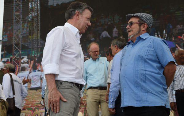 """Guerrilheiro das FARC Rodrigo Londono Echeverri, conhecido como """"Timochenko"""" (de) e o ex-presidente colombiano Juan Manuel Santos conversam no município de Mesetas, Colômbia, em 27 de junho de 2017 (RAUL ARBOLEDA / AFP / Getty Images)"""