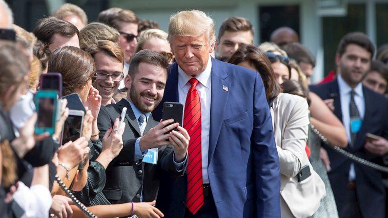 O presidente dos Estados Unidos, Donald Trump (c), tira uma foto com vários apoiadores após sua chegada à Casa Branca, nesta quinta-feira(26) em Washington (foto EFE / Erik S. Lesser)