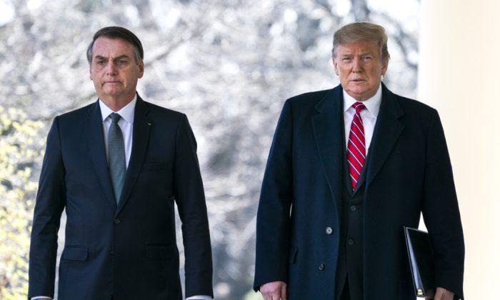El presidente de Estados Unidos Donald Trump (Der) y el presidente de Brasil Jair Bolsonaro (Izq) caminan por el Colonnade antes de una conferencia de prensa en el Jardín de Rosas de la Casa Blanca en Washington, DC el 19 de marzo de 2019. (Getty Images)