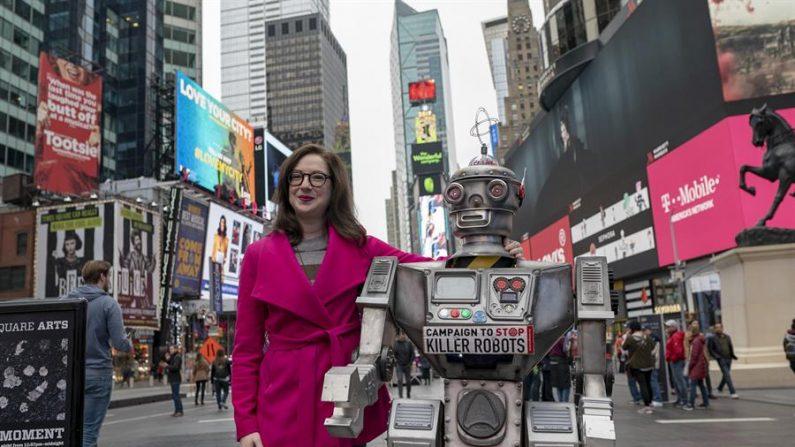Campaña Para Detener los Robots Asesinos donde aparece una de sus integrantes, la experta Liz O'Sullivan, mientras posa junto a un robot el 20 de octubre en Times Square, Nueva York (EE.UU.). EFE/Ari Beser/Campaign to Stop Killer Robots