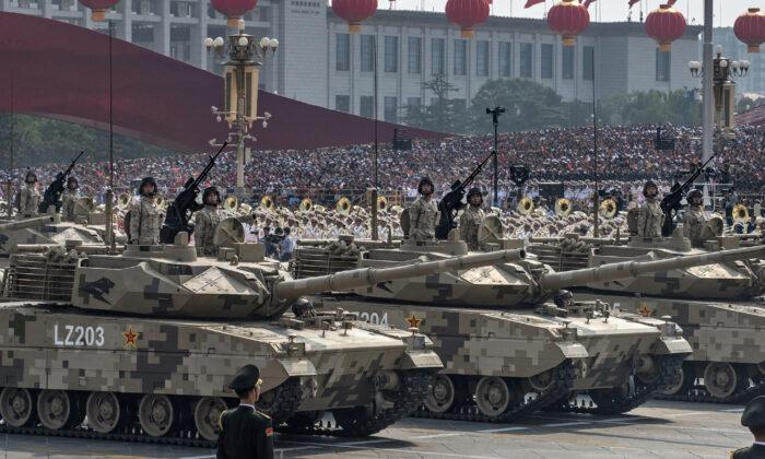 Soldados chinos apostados arriba de tanques mientras conducen en un desfile para celebrar el 70º aniversario de la toma de poder de China por parte del Partido Comunista, en la Plaza de Tiananmen en Beijing, el 1 de octubre de 2019. (Kevin Frayer/Getty Images)