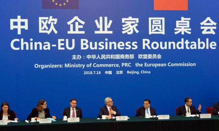 El primer ministro de China, Li Keqiang (segundo desde la derecha), mira al presidente de la Comisión Europea Jean-Claude Juncker (centro) durante la Mesa Redonda de China-UE en el Gran Salón del Pueblo, Beijing, 16 de julio de 2018. (Ng Han Guan /AFP/Getty Images)