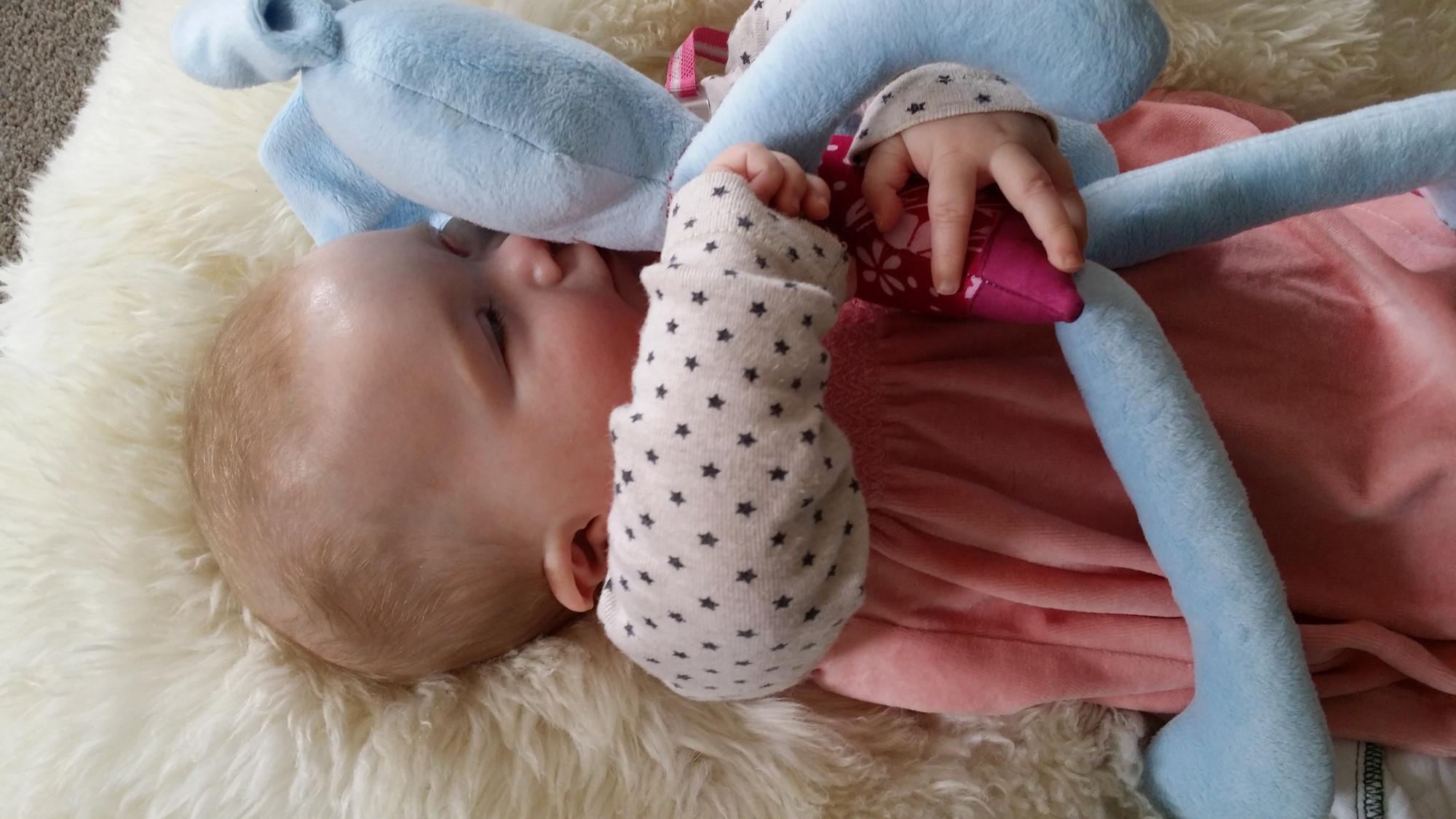 Eva besando a su conejito azul hecho por su tía, y acostada sobre una piel de oveja en su casa que compartió con su madre y otra familia.