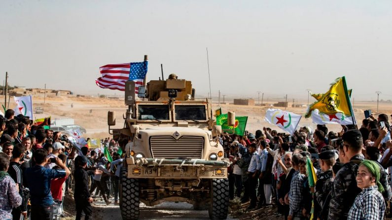 Los kurdos sirios se reúnen alrededor de un vehículo blindado estadounidense durante una manifestación contra las amenazas turcas junto a una base de la coalición internacional liderada por Estados Unidos en las afueras de la ciudad de Ras al-Ain, en la provincia siria de Hasakeh, cerca de la frontera con Turquía, el 6 de octubre de 2019. (DELIL SOULEIMAN/AFP vía Getty Images)