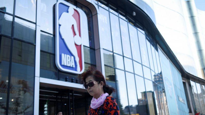Una mujer camina junto a una tienda de productos de la NBA en Beijing el 8 de octubre de 2019. (Wang Zhao/AFP a través de Getty Images)