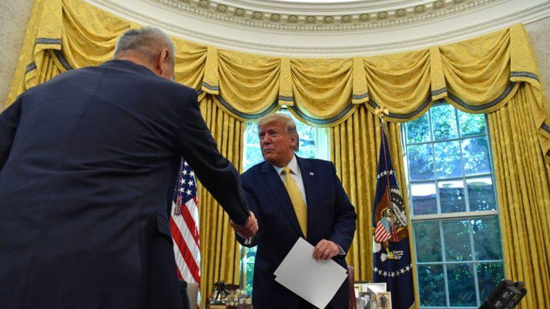 El viceprimer ministro chino Liu He (I) entrega una carta del líder chino Xi Jinping al presidente Donald Trump en la Oficina Oval de la Casa Blanca en Washington, el 11 de octubre de 2019. (NICHOLAS KAMM/AFP a través de Getty Images)