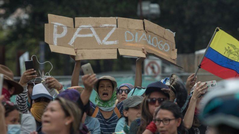 """Un manifestante sostiene un cartel que dice """"Paz y diálogo"""" mientras mujeres de diferentes partes de Ecuador marchan por las calles de Quito para pedir paz y derogar las medidas económicas tomadas por el presidente de Ecuador, Lenin Moreno, sobre 12 de octubre de 2019 en Quito (Jorge Ivan Castaneira Jaramillo/Getty Images)"""