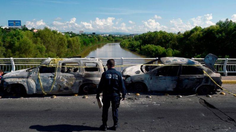Un policía se para junto a vehículos quemados después de que narcos fuertemente armados libraron una batalla total contra las fuerzas de seguridad mexicanas en Culiacán, estado de Sinaloa, México, el 18 de octubre de 2019. (ALFREDO ESTRELLA/AFP vía Getty Images)
