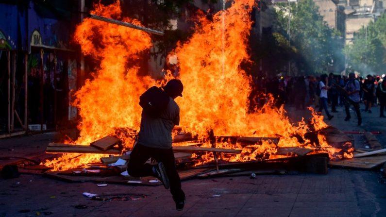 """Manifestantes queman una barricada durante una protesta en Santiago de Chile el 21 de octubre de 2019. - El número de muertos en Chile ha aumentado a 11, dijeron las autoridades el lunes, después de tres días de violentas manifestaciones y saqueos que hicieron que el presidente Sebastián Piñera afirmara que el país estaba """"en guerra"""". (Foto de MARTIN BERNETTI/AFP vía Getty Images)"""