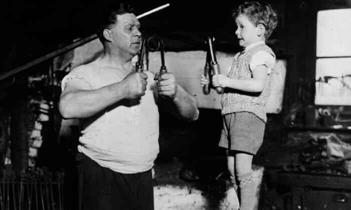 Un niño y su padre fortaleciendo sus músculos  (Photo by Fox Photos/Getty Images)