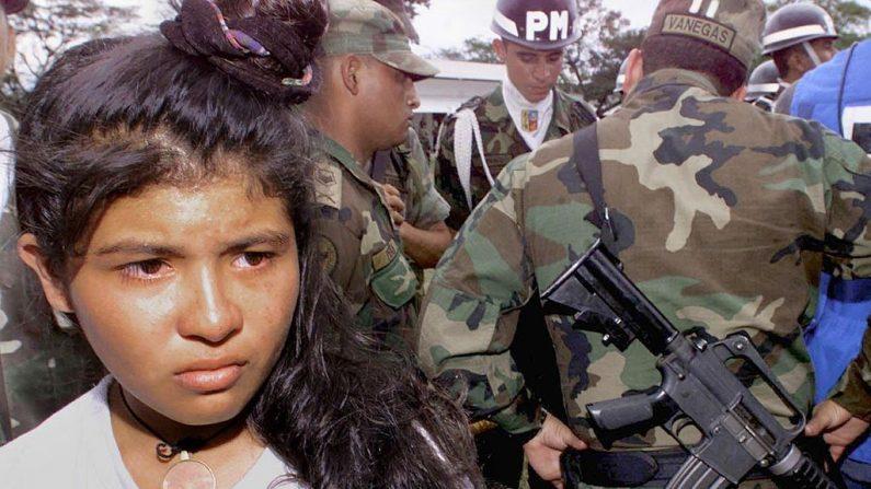 Una guerrillera colombiana de 15 años es rescatada y retenida el 16 de enero de 2000 en la base de la fuerza aérea de Apiay, provincia de Meta, luego de ser capturada durante enfrentamientos entre soldados colombianos y guerrilleros de las Fuerzas Armadas Revolucionarias de Colombia (FARC) (LUIS ACOSTA / AFP / Getty Images)