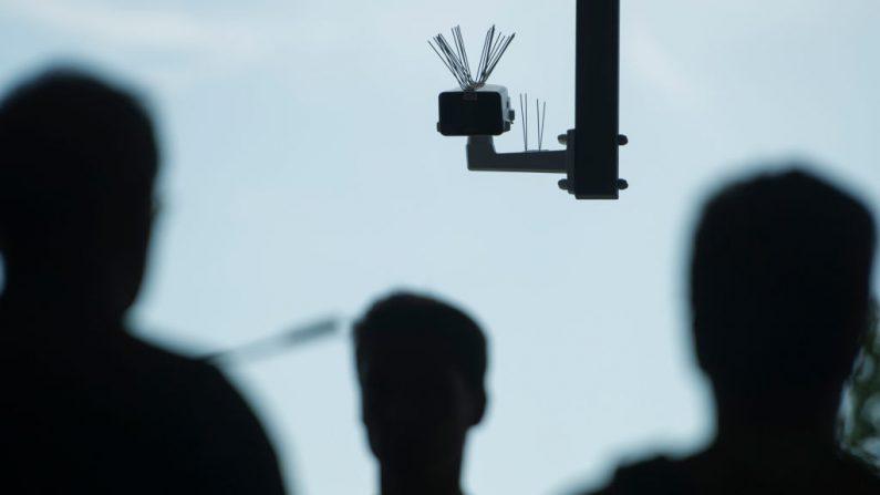 Transeúntes caminan bajo una cámara de vigilancia que es parte de una prueba de tecnología de reconocimiento facial. (Steffi Loos/Getty Images)
